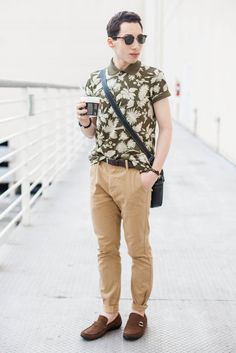 Shop this look on Lookastic:  http://lookastic.com/men/looks/polo-belt-driving-shoes-sunglasses-messenger-bag-chinos/6477  — Olive Floral Polo  — Dark Brown Leather Belt  — Brown Suede Driving Shoes  — Dark Brown Sunglasses  — Black Leather Messenger Bag  — Khaki Chinos