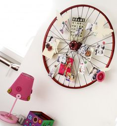 Old bike wheel turned into a pin board. The verdict is still out on this. One part of me thinks it is pretty creative and the other is not sold on how practical it really is. I have seen clothes pins used for attaching things also.
