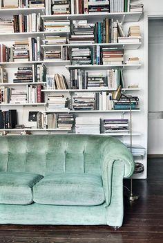 Un canapé en velours vert d'eau dans le salon
