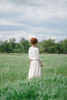 Beautiful young redhead woman standing in a field in a white dress by Stalman & Boniecka