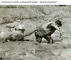 havo: hier is een soldaat die in de modder is blijven hangen een ander soldaat help hem om uit de modder te komen. Vietnam oorlog