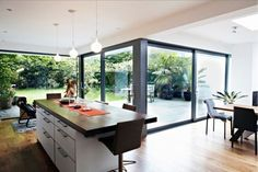 glass extension kitchen space - glass wall corner and skylight over dining table.