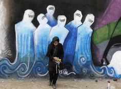 Beyond the burqa: Shamsia Hassani clears rubbish from in front of one of her graffiti creations in an industrial park in Kabul. Photograph: © Omar Sobhani/Reuters