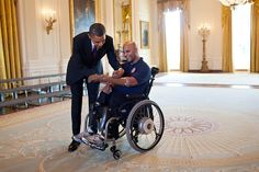 President Barack Obama signs the prosthetic arm of Sgt. Carlos Evans, USMC, after greeting wounded warriors in the East Room during their tour of the White House, March 6, 2012. First Lady Michelle Obama first met Evans, who was injured in Afghanistan while on his fourth combat deployment, during a visit to Walter Reed Army Medical Center in 2010. (Official White House Photo by Pete Souza)