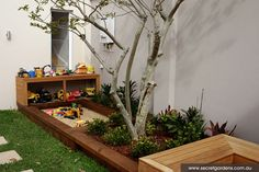 Family Friendly Gardens nice way to incorporate sandpit - and to hide/protect sandpit toys!