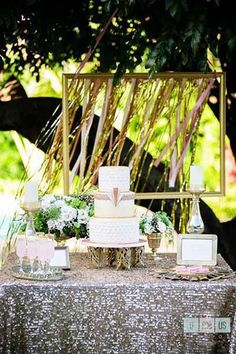 Use vintage furniture pieces like this gold bar cart to fit the time. A sequined tablecloth and Art Deco detailed cake make for a 1920s-inspired dessert table.