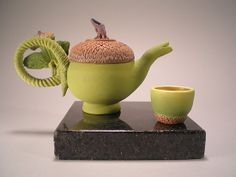 """Green Acorn Tea with Cup""  Ceramic Teapot    Created by Nancy Y. Adams  Wheel thrown porcelain teapot and cup. Sculptural/nonfunctional. Easily cleaned by rinsing in water and allowing to air dry."