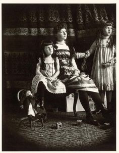Three sisters posing with their blocks and doll, 1890.