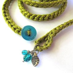 Crochet wrap bracelet or necklace made of cotton yarn in a lovely light shade of olive featuring glass bead and metal charms. This fun and versatile accessory is approximately 67 long and wraps about 9 times around a 6.5 - 7 wrist. This fun wrap also makes a simple, soft necklace that can be worn wrapped, knotted, layered and many other ways around your neck - let your imagination guide you! Closes with a loop and button  Hand wash in cool water, gently stretch to reshape, dry flat  This…