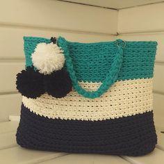 Novidade ! Bolsa ovalada em fio de malha com pompom . O verão está chegando e ela pode ser usada na praia, piscina ... Escolha a sua cor #fiodemalha #trapillo #trapilho #bolsadecroche #pompom #bolsacompompom