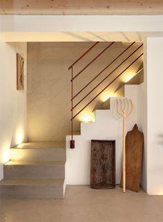 Los materiales modernos usados en la construcción mitigan la atmósfera rústica de la casa y van tejiendo un nexo cromático entre los distintos espacios. El rincón de la escalera que sube hacia el entrepiso – resaltado por una serie de spots empotrados que crean un efecto teatral– mezcla en partes iguales el cemento alisado en tonos beige con el blanco de las paredes. Enmarcadas por la silueta geométrica de la escalera, unas herramientas de trabajo antiguas dispuestas en clave escultórica… Room Partition Designs, Country Interior, Spanish House, New Home Designs, Staircase Design, My Dream Home, Interior Architecture, New Homes, Interior Decorating