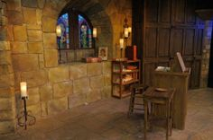 "This photos shows the transformation from a construction drawing to real-life construction. It also shows a great view of fake stone. For this set, stones were cut out of approx 1/2"" thick foam and individually applied, then painted in place. The linen-fold paneling to its right is made from plywood, 1x4 lumber for the ""frames"" and, again, foam for the carved panels. Also painted and wood-grained in place. The carpenters and painters did a fantastic job!"