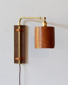 The custom-made Ava Wall Sconce has a black walnut back plate, a brass arm, and a hand sewn leather shade. The brass arm articulates to fulfill many different lighting needs. It can provide up lightin