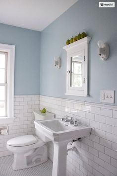 Wall paint: Fantasy Blue, Benjamin Moore; Cartwright inset medicine cabinet: Restoration Hardware; wall tile: 3-inch-by-6-inch subway tiles in Arctic White with semigloss finish, Daltile; tile cap: 1½-inch-by-6-inch Melody chair rail in Arctic White 0190 with semigloss finish, Simple Elegance line, Daltile; flooring: 1-inch hexagonal tiles with matte finish, via Powerline Imports;