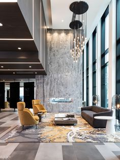 A Durkan rug with a chandelier and sofa by Restoration Hardware define the lobby seating area, with a coffee table from Seasonal Living and porcelain tile fireplace surround by Thorn Tree