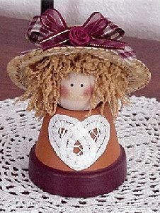 """You will need:     1- 1 1/2"""" diameter wooden ball  1- 2 1/4"""" diameter clay pot  straw hat 4"""" brim  12"""" of 1/4""""-1/2"""" wide sheer maroon ribbon with gold accent  12"""" of 1/2""""-3/4"""" wide maroon gingham ribbon  heart cut from paper doily  small maroon silk rose  tan nubby yarn  acrylic paints in flesh, maroon, and pink  Black Sharpie fine or medium point marker  scissors  Tacky Glue  Hot glue gun           Place newspaper down on work surface. Turn clay pot over and glue wooden ball to bottom of…"""