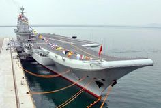 Liaoning at its home port of Qingdao, Nov. 26, 2013.  China's first aircraft carrier battle group is expected to be formed next year to make up for the shortcoming of the limited combat radius of the country's existing fleets, according to China's official news agency Xinhua.  Citing the Military-Industrial Courier, a Russia-based weekly, the report said China's first carrier, the Liaoning, embarked on its first blue-water passage in early 2014 escorted by 12 vessels of different classes.