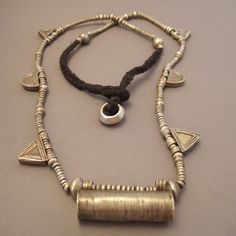 Africa | A silver 'Telsum' necklace from Ethiopia | talisman tubular, triangular elements and wedding ring at the very end of the necklace are all symbols of protection for the wearer