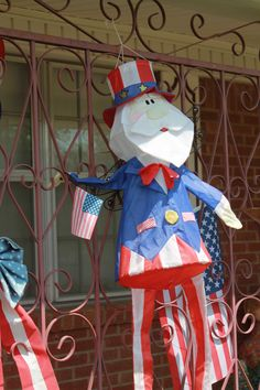 Towards the back half of the front porch I have an Uncle Sam wind sock hanging outside the bars. I also have of July bows mounted to the outside of the bars. Wind Socks, Porch Decorating, Front Porch, 4th Of July, Disney Characters, Fictional Characters, Bows, Art, Balcony Decoration