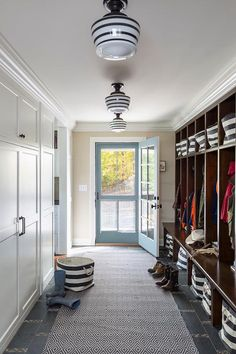lighting Long country style mudroom features a wall lined with open stained mudroom lockers accented with rugby stripe bins from the Container store both below each seat and above on the top of each shelf for extra storage and enhanced organization.