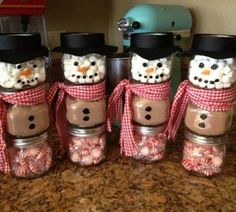 December or Jan Craft - Snowman made from a baby food jar. The top jar is filled with marshmallows. The middle jar is filled with hot chocolate mix. The bottom jar is filled with mints.