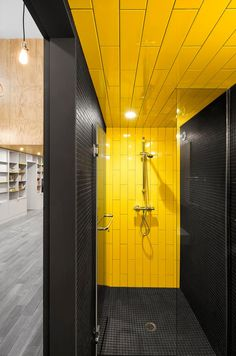 A shower with yellow and grey tiles- a perfect combination for the modern home.
