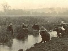 """Boys at Play. A convenient stream provides the perfect """"No Mans Land"""" across which a group of young boys, in assorted military headgear, play a pretend battle. HMCMS:DPAAIX47"""