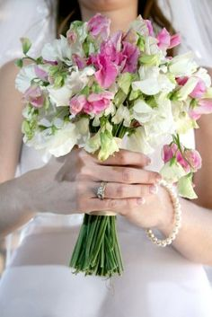 Very dainty hand tied wedding bouquet of white and pink sweet peas.