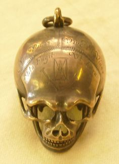 Silver cased verge watch in the form of a human skull, engraved with memento morie exhortations. (Ashmolean Museum)