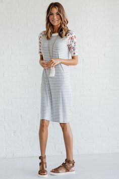 The Vacay Bound Floral Grey Striped Dress is a gorgeous midi dress! Our dress features half-length sleeves, a high, rounded neckline, light gray and white stripes, and a floral print on the sleeves that includes pops of cherry red, blush pink, lavender purple, navy blue, and cream. You are going to want to wear the Vacay Bound Floral Grey Striped Dress to all of your end of summer and fall events!