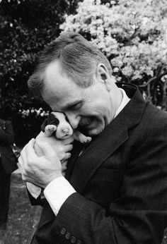 President George H.W. Bush snuggles with one of first dog Millie's six puppies on March 29, 1989, at the White House.