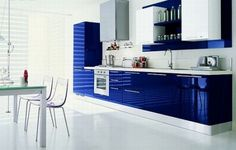 Sleek Blue kitchen with stark white walls and floors! right down to the transparency in furniture. Clean, straight lines and no fuss. Perfect sleek kitchen
