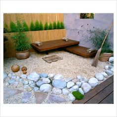 Roof garden with bamboo fence, white boulders, Red Cedar deck and seats, rendered wall with window and besom broom