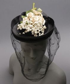 Woman's Hat  Designed by G. Howard Hodge, American. Sold by Harold, Inc., Minneapolis Date: c. 1944 Medium: Black straw, artifical flowers, veiling, black velvet ribbon  Accession Number: 1967-101-29