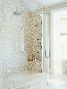 A seamless curved door on this two-person shower allows natural light to flood the area and showcases the tiled walls. The neutral color of the mosaic tiles brings serenity to the room. The area's limestone floor isn't just an attractive surface -- it's heated for comfort.