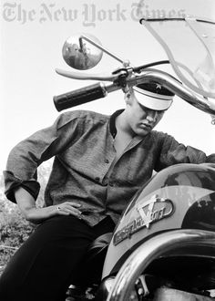 Elvis Presley on his Harley-Davidson motorcycle, wondering why it wouldn't start. Answer: no gas in the tank. At his home at 1034 Audubon Drive, Memphis, July 4, 1956. Part of the legendary collection of images of Elvis Presley taken by Alfred Wertheimer in March and July, 1956, when the singer went from virtual obscurity to international fame.