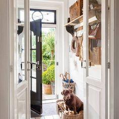 Recibidor en blanco con colgadores de madera, cestas, cajas, paragüero y perro.