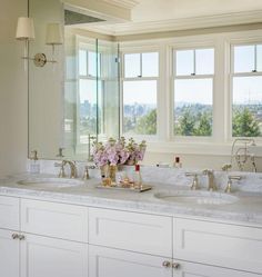 Tan walls hold a large frameless vanity mirror finished with Bryant sconces mounted to the mirror as a double vanity boasting white shaker cabinetry accented with polished nickle hardware, gray and white marble countertops, and polished nickle faucets complete this gorgeous master bathroom.