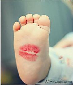 Beso de mamá. Fotografía original pie del bebé. Foto tierna madre hijo