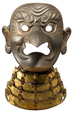 Iron Tengu Somen by Myochin Muneharu.Edo period (17th century) The face plate forged in one piece and the nose and ears separately forged and riveted together, the surface finished in a russet patina and hammered up with prominent wrinkles and eyebrows held in a scowl, with two pegs for cords and one ventilation hole on the chin, the interior lacquered black and red signed Myochin (no) ki Muneharu. Fitted with a four-lame yodarekake lacquered gold and laced in orange