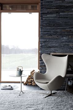 stacked slate stone wall, large tile flooring, ...love the mod chair