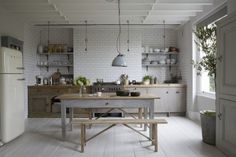 Neutral open plan kitchen diner, white wood beam ceiling, vintage rustic bench and table, fitted units, metro ceramic brick wall tiles, Smeg cooker, pendant light, painted floorboards L etc 02/2014