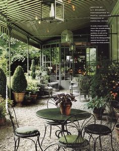Pierre Berge's garden in Paris. The veranda which connects the two pavilions. The cafe table and chairs are by Diego Giacometti. Photo by Pascal Chevallier.