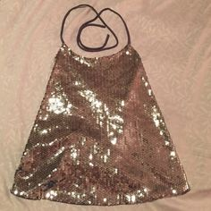 Sequence top NWOT Sequins all around the top ties around the neck and has two ties down the back. In perfect condition never worn. NWOT :) Tops