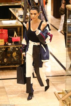 Find something she liked? Kourtney was seen holding a black shopping bag...