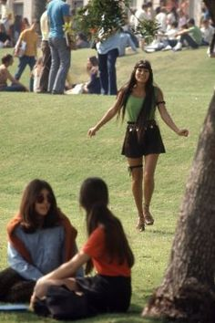 View of a Southern California high school student as she walks on the grass dressed in a green tanktop and a miniskirt, accented with a headband, armband, and a thighband, October 1969. [Miniskirt styles of the '60s and '70s | SF Unzipped | an SFGate.com blog]
