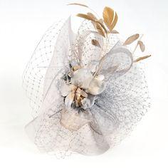 tocado de fiesta con rejilla, cintas y plumas en color blanco y beig.