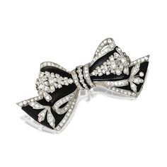PLATINUM, DIAMOND AND ONYX BOW BROOCH, CIRCA 1915 The stylized bow brooch composed of onyx sections, edged and overlaid with platinum, set with old European-cut and single-cut diamonds.