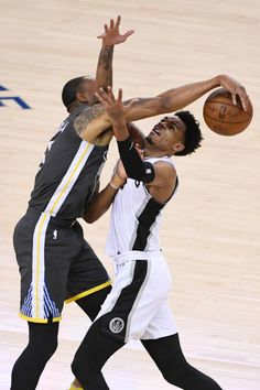 Golden State Warriors' Andre Iguodala (9), left, fights for a ball with San Antonio Spurs' Dejounte Murray (5), right, during the first quarter of Game 2 of their NBA first-round playoff series at Oracle Arena in Oakland, Calif., on Monday, April 16, 2018. (Jose Carlos Fajardo/ Bay Area News Group)