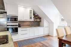 weiße Küchenfronten mit Stahl Griffen und dunkler Fliesenspiegel